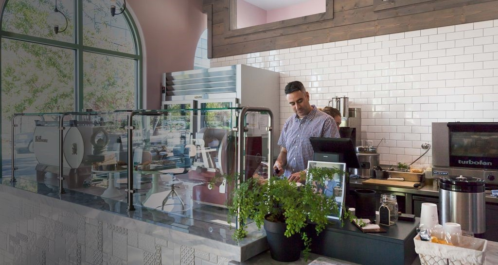 Mike Fagnoni behind the counter working at Hawks Provisions